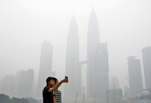 Tourists take a selfie against Malaysia's landmark building Petronas Twin Towers shrouded with haze in Kuala Lumpur, Malaysia on Saturday, Sept. 26, 2015. Malaysian authorities reported four areas in Peninsular Malaysia hits an unhealthy API (air pollution index). (AP Photo/Joshua Paul)